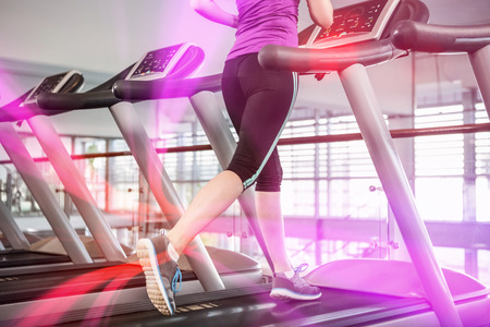 Lower section of fit woman on treadmill at gym