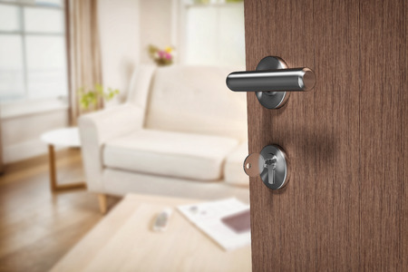 Brown door with key against sitting room Stock Photo