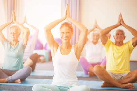 Portrait of instructor performing yoga with seniors during sports class Stock Photo