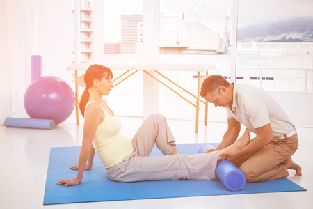 Physiotherapist giving physiotherapy to pregnant woman on exercise mat