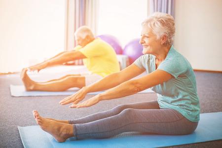 Seniors stretching legs in studio
