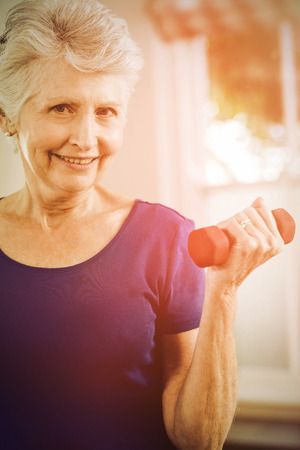 Portrait of senior woman exercising with dumbbells at home Stock Photo