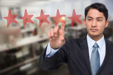 Stern asian businessman pointing against empty computer room