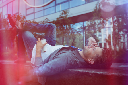 Handsome business executive lying talking on mobile phone while lying on retaining wall