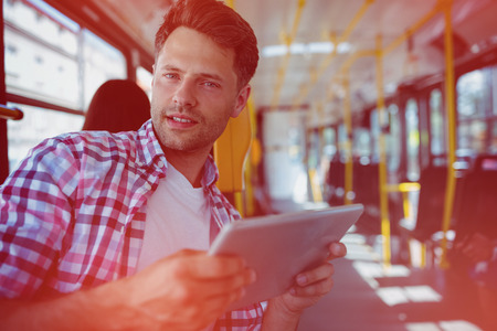 Portrait of handsome man holding digital tablet in bus Stock Photo