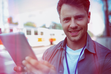 Portrait of cheerful business executive using digital tablet on road Stock Photo