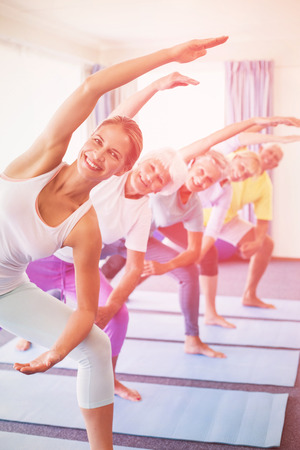 nursing class: Portrait of instructor performing yoga with seniors during sports class Stock Photo