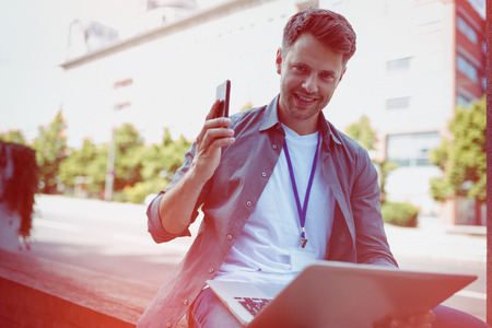 Portrait of handsome business executive holding mobile phone and laptop Stock Photo