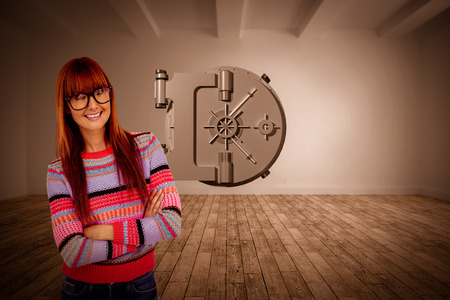 Portrait of a smiling hipster woman with arms crossed against digital room