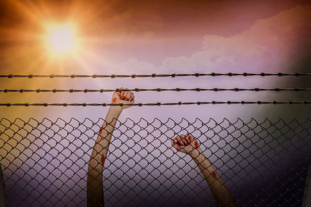 Laughing teenage wearing casual clothes while raising her arms against barbed wire and chainlink fence against white background