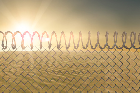 barbed wire fence: Barbed wire fence by white background against desert scene Stock Photo
