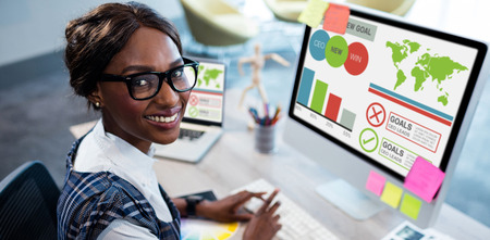 Digitally generated image of business presentation with charts and text against woman working on computer while sitting at office Stock Photo