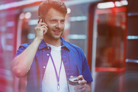 Handsome holding disposable cup while talking on mobile phone at plat form