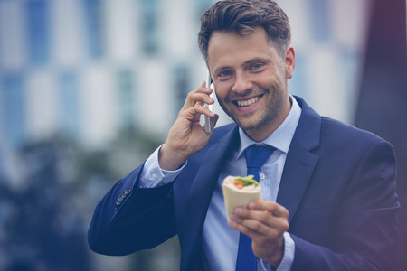 Portrait of handsome businessman holding wrapped sandwich while talking on mobile phone Stock Photo