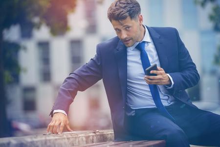 Portrait of stylish businessman using digital tablet on retaining wall