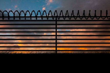 Digitallly generated image of barbed wire on fence against cloudy sky 3d