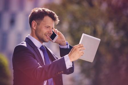 Handsome businessman using mobile phone and digital tablet
