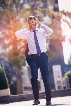 Portrait of confident businessman talking on mobile phone while walking on road Stock Photo