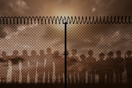Digitally generated image of fence with spiral barbed wire against blue and orange sky with clouds Stock Photo