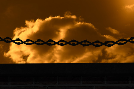spiked: Silhouette image of barbed fence wire against cloudy sky Stock Photo
