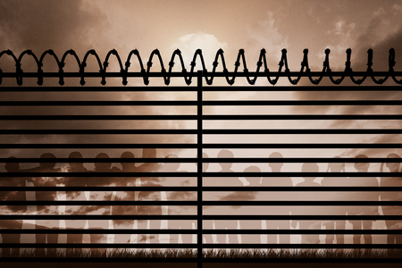 curled up: Graphic image of spiral barbed wire on fence against cloudy sky Stock Photo