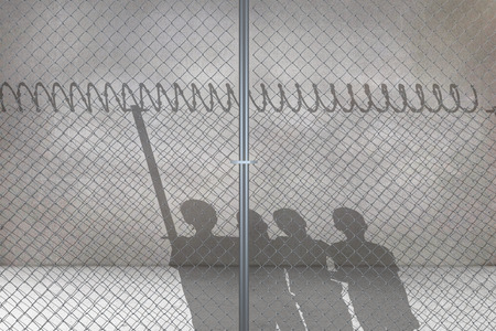 Chainlink fence by white background against grey room