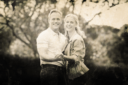 Grey background against happy couple holding hands against trees