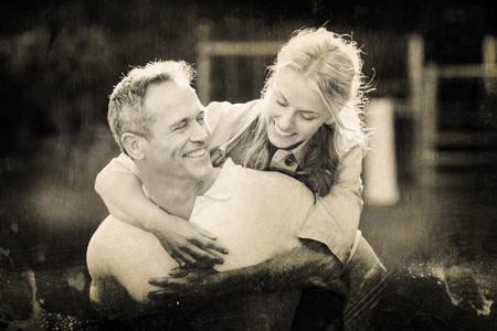 Grey background against husband giving piggy back to wife Stock Photo