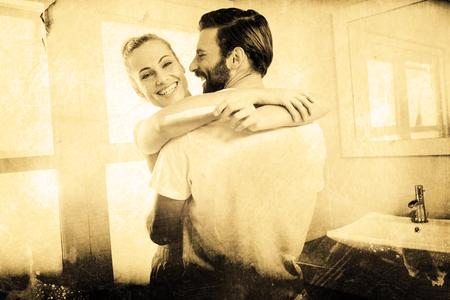prueba de embarazo: Grey background against woman holding pregnancy test while embracing man Foto de archivo