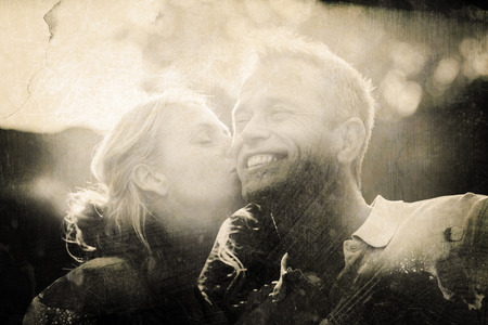 Grey background against wife kissing husband on cheek