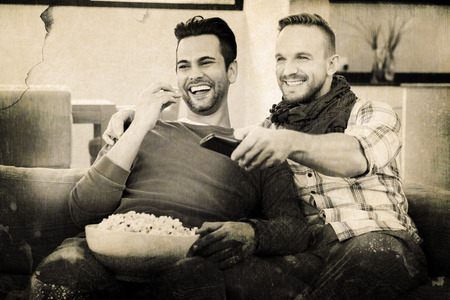 Grey background against gay couple watching television with pop corn