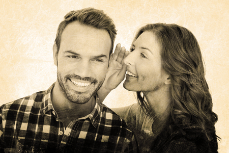 Grey background against woman whispering into mans ears Stock Photo