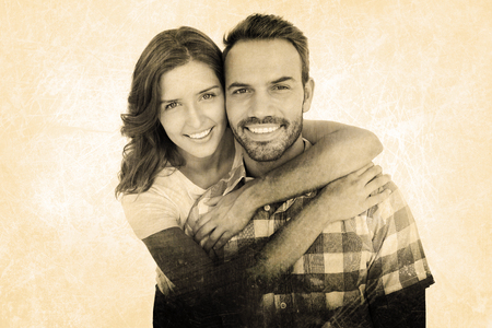 Happy young couple embracing against grey background