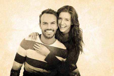 Portrait of cheerful young couple embracing against grey background