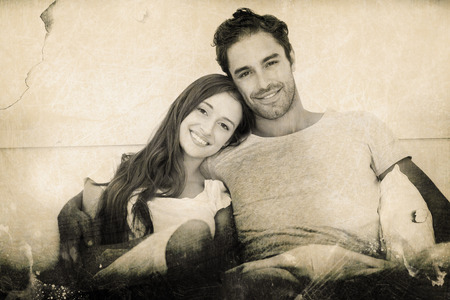 Grey background against portrait of happy couple leaning on bed