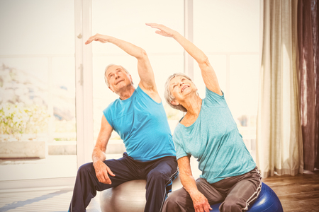 Senior couple with arms raised while performing exercise at home