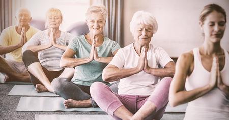 체육 수업 중 노인들과 함께 요가를하는 강사 스톡 콘텐츠