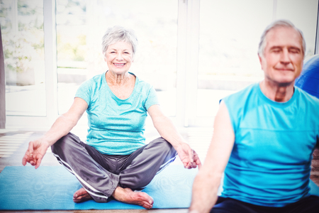 Portrait of happy senior woman with husband meditating at home Stock Photo