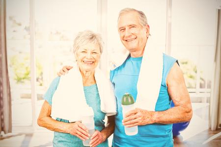 Portrait of happy senior couple holding bottle while exercising at home