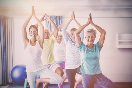 hospedaje: Instructor de yoga con la realización de la tercera edad durante la clase de deportes Foto de archivo