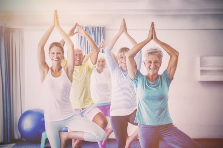 70s: Instructor performing yoga with seniors during sports class
