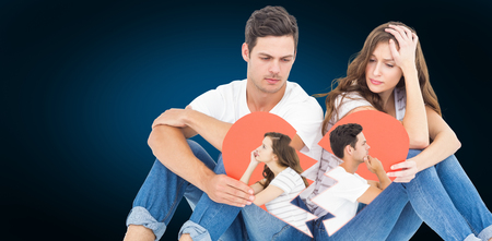 Thoughtful couple sitting on floor back to back against blue background with vignette