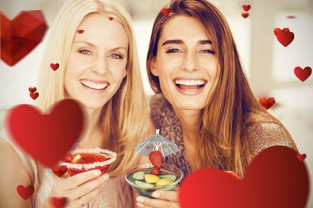 Portrait of beautiful women having mocktail against love heart pattern