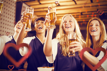 Low angle view of friends holding glass of beer in party against hearts