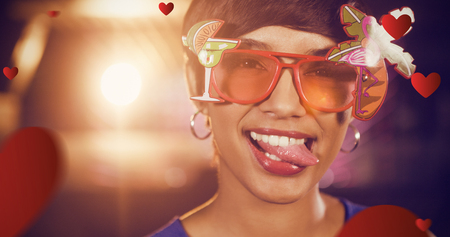 Woman wearing fancy sunglasses making funny faces in bar against hearts