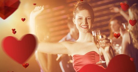 Portrait of young woman holding glass of champagne while dancing against love heart pattern