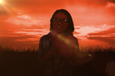 red sky: Asian woman holding paper heart against red sky over grass