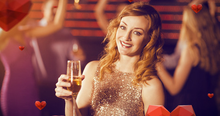 Portrait of young woman holding a glass of champagne against hearts