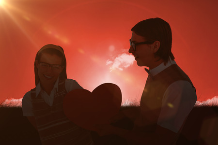 together with long tie: Geeky hipster offering red heart to his girlfriend  against red sky over grass