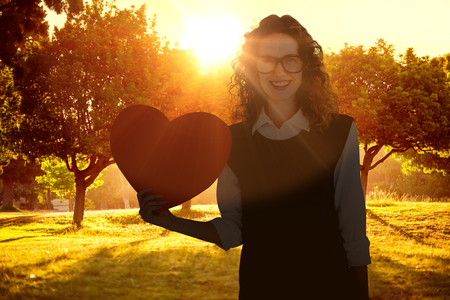 Geeky hipster holding heart card against sunrise over trees Stock Photo